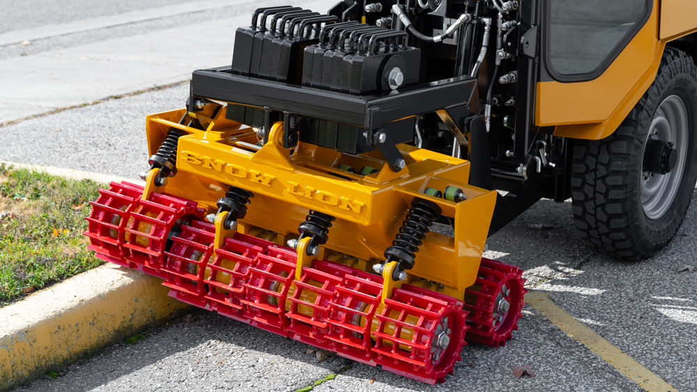trackless vehicles snow lion ice-breaker on sidewalk tractor attachment close-up