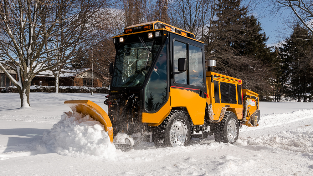 trackless vehicles double trip plow attachment on sidewalk tractor in snow front view