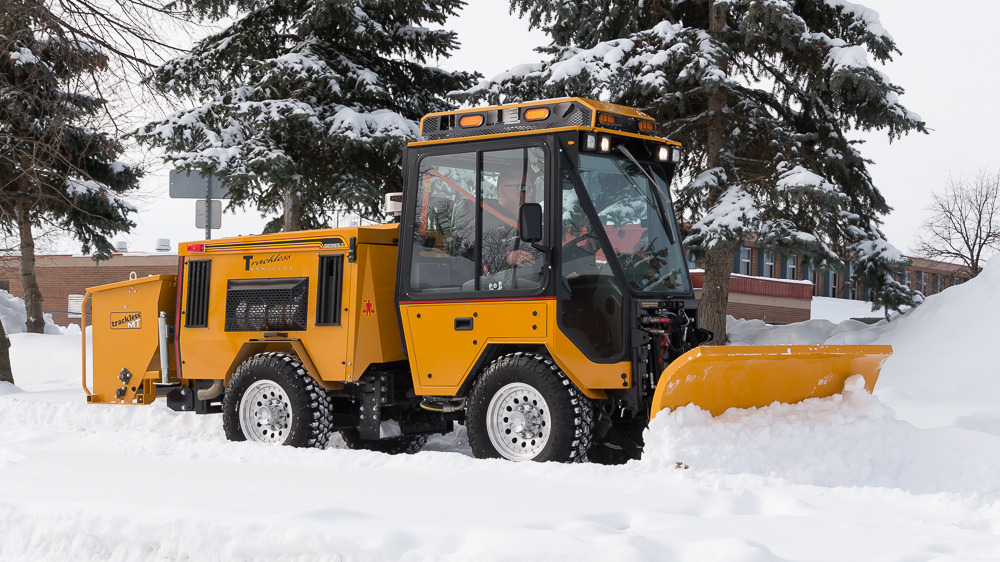 trackless vehicles double trip plow attachment on sidewalk tractor in snow side view