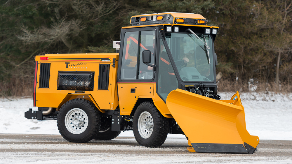 trackless vehicles fixed wing v-plow attachment on sidewalk tractor in snow side view