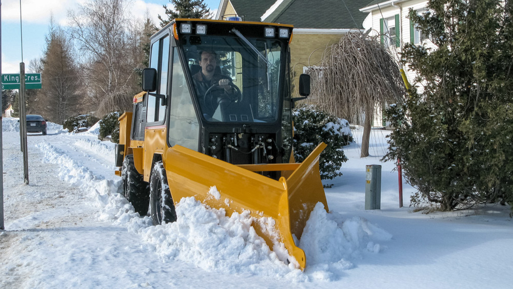 trackless vehicles fixed wing v-plow attachment on sidewalk tractor in snow front view