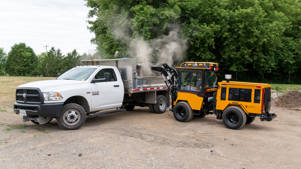 trackless vehicles front end loader attachment on sidewalk municipal tractor dumping dirt into truck