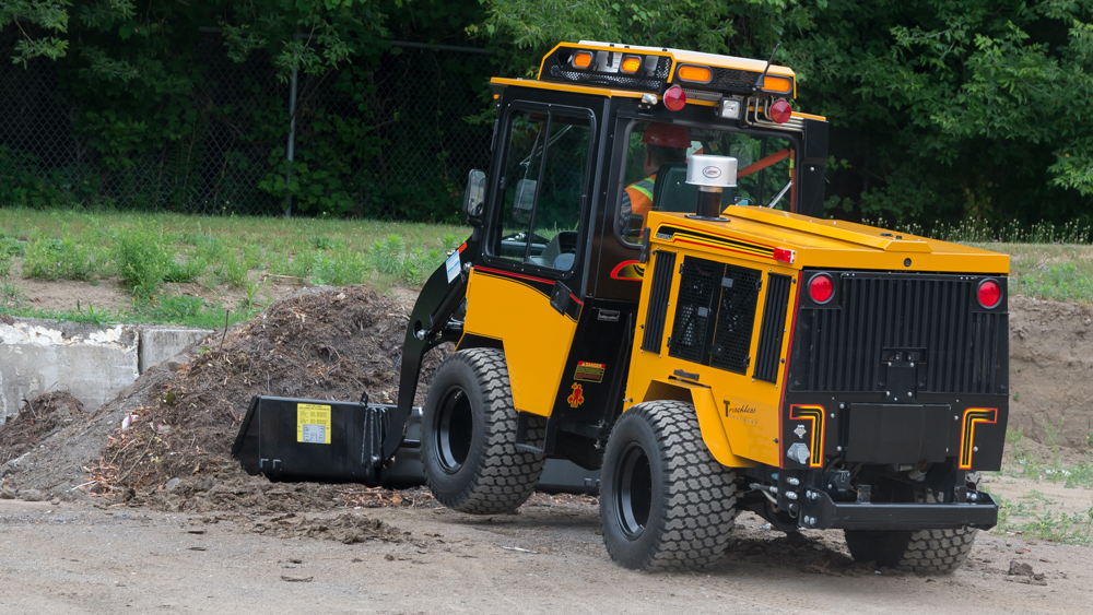 trackless vehicles front end loader attachment on sidewalk municipal tractor rear side view