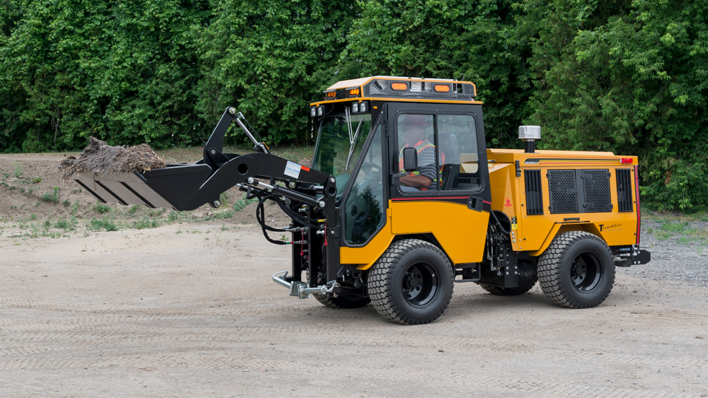 trackless vehicles front end loader attachment on sidewalk municipal tractor carrying dirt side view