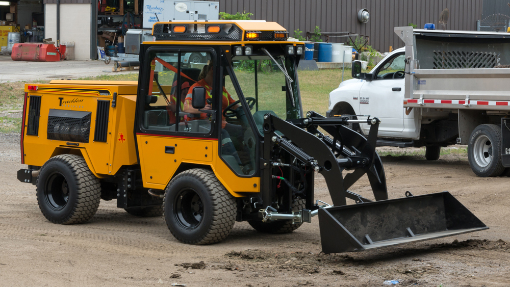 trackless vehicles front end loader attachment on sidewalk municipal tractor side view