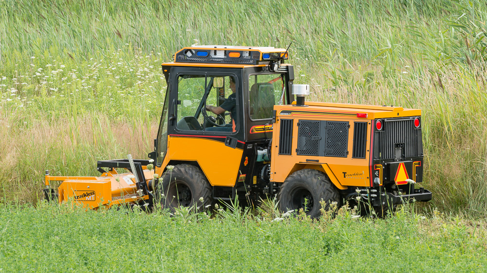 trackless vehicles front flail mower attachment on sidewalk municipal tractor mowing grass side rear view