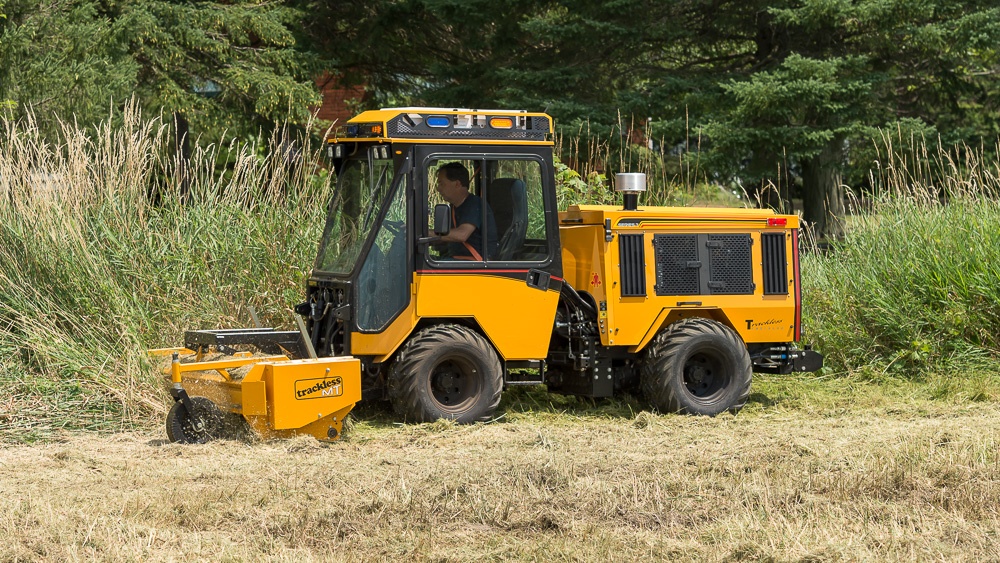 trackless vehicles front flail mower attachment on sidewalk municipal tractor mowing grass side view