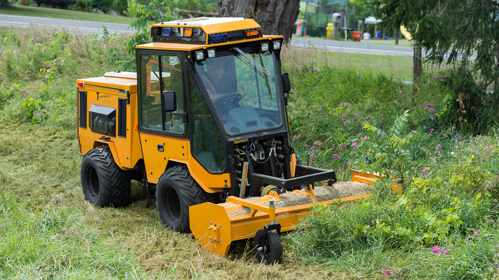 trackless vehicles front flail mower attachment on sidewalk municipal tractor mowing grass side front view