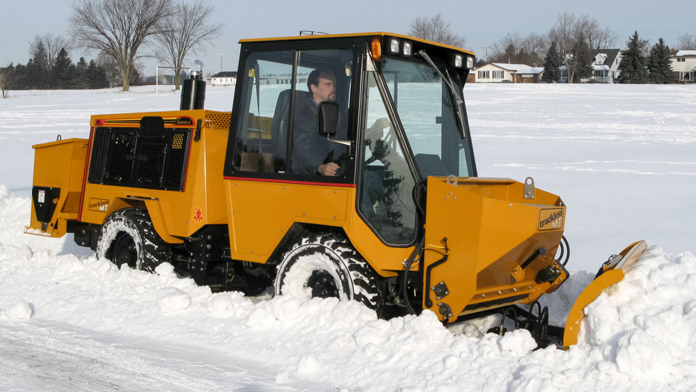 trackless vehicles front-mount spreader and plow attachment on sidewalk tractor in snow side view