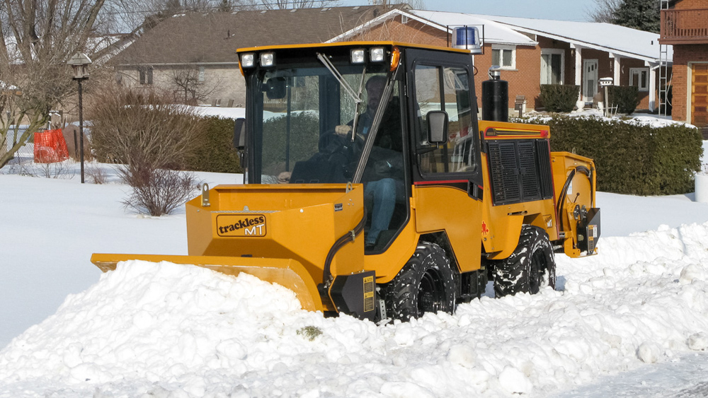trackless vehicles front-mount spreader and plow attachment on sidewalk tractor in snow front view