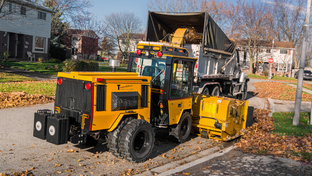 trackless vehicles leaf loader attachment on sidewalk municipal tractor loading leaves rear side view