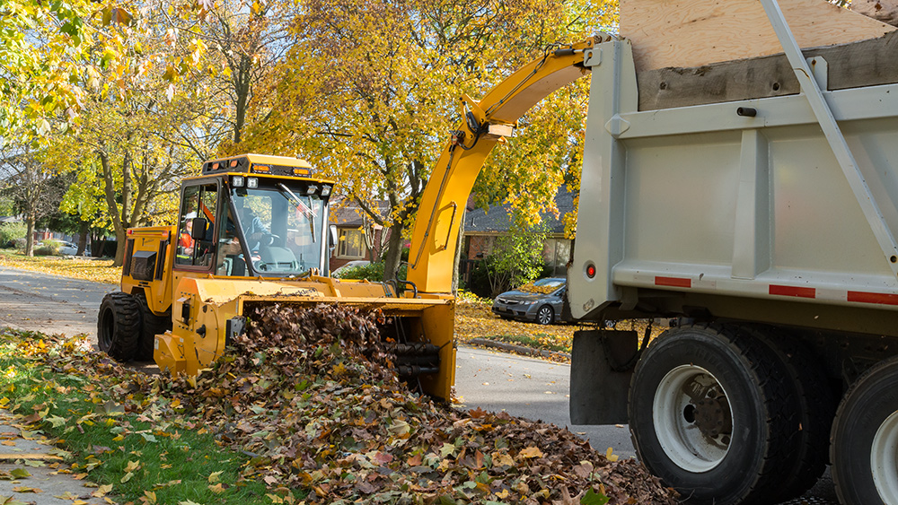 trackless vehicles leaf loader attachment on sidewalk municipal tractor loading leaves front view