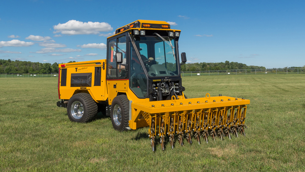 trackless vehicles aerator attachment on sidewalk municipal tractor in field front side view