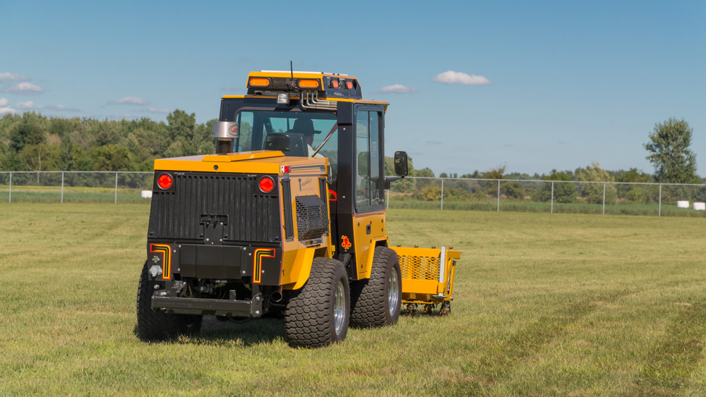 trackless vehicles aerator attachment on sidewalk municipal tractor in field rear view