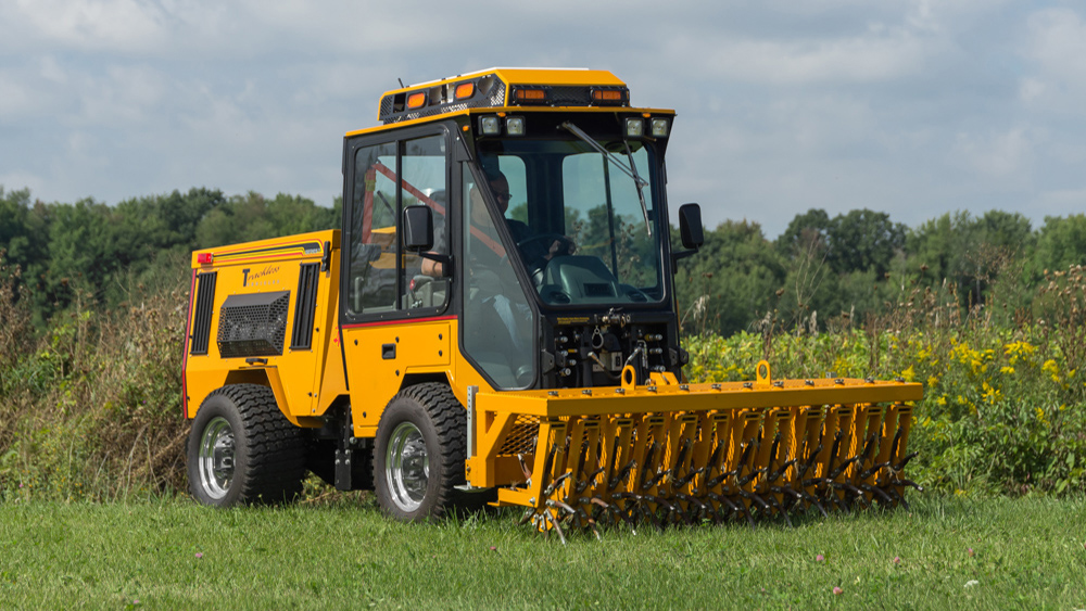 trackless vehicles aerator attachment on sidewalk municipal tractor front side view