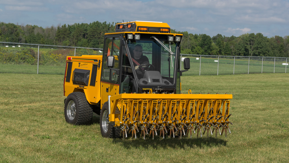 trackless vehicles aerator attachment on sidewalk municipal tractor front view