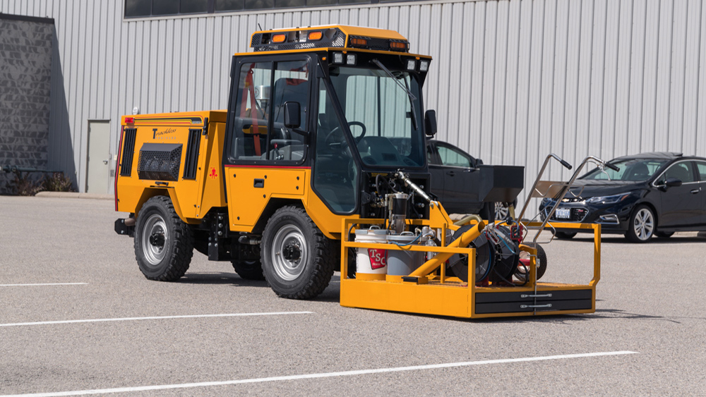 trackless vehicles line and stencil painter attachment on sidewalk tractor side view