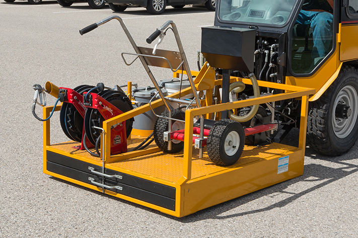 trackless vehicles line and stencil painter attachment on sidewalk tractor front view
