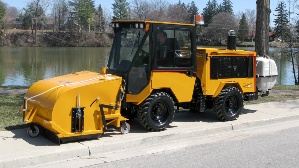 trackless vehicles pickup sweeper attachment on sidewalk municipal tractor side view