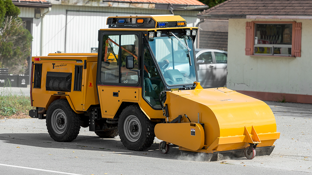 trackless vehicles pickup sweeper attachment on sidewalk municipal tractor working on sidewalk