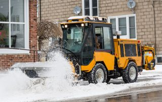trackless vehicles power angle sweeper attachment on sidewalk municipal tractor working on sidewalk in snow side view