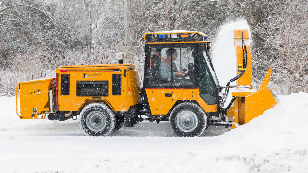 trackless vehicles ribbon snowblower attachment on sidewalk tractor in snow