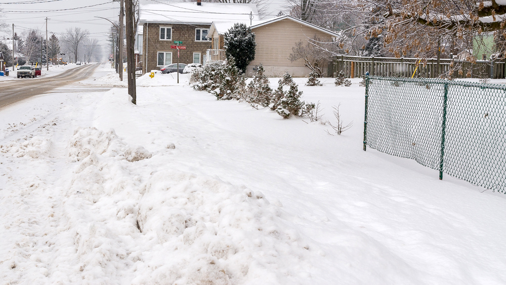 snow on ground before trackless vehicles 5-position folding v-plow attachment on sidewalk tractor