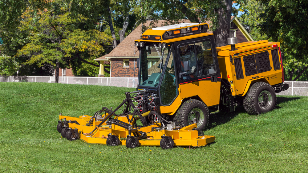 trackless vehicles rotary finishing mower 14' attachment on sidewalk municipal tractor mowing grass front side view