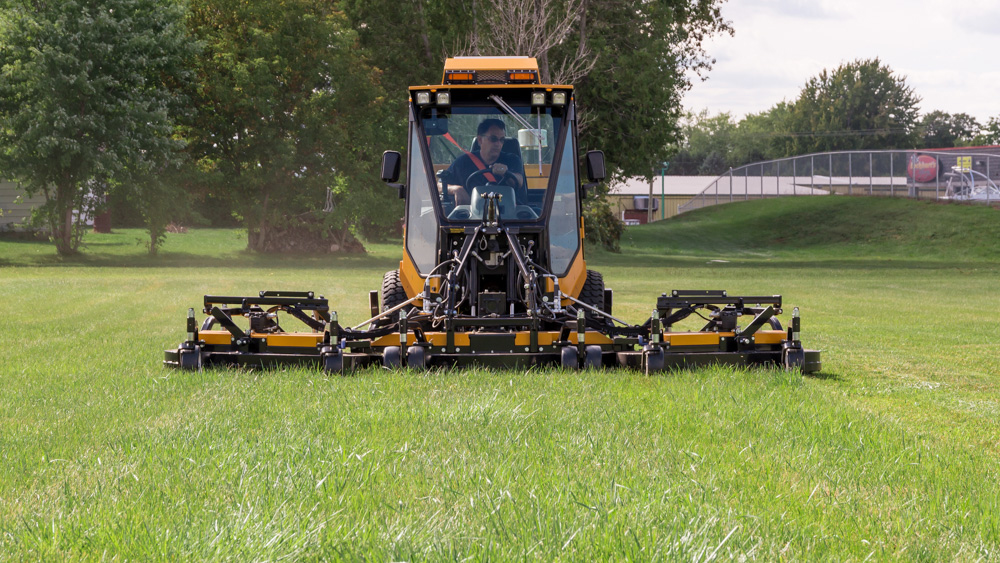 trackless vehicles progressive turf 14' mower attachment on sidewalk municipal tractor mowing grass front view