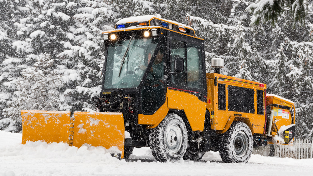 trackless vehicles 5-position folding v-plow attachment on sidewalk tractor in snow side front view