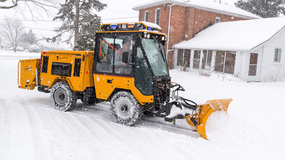trackless vehicles 5-position folding v-plow attachment on sidewalk tractor in snow side view