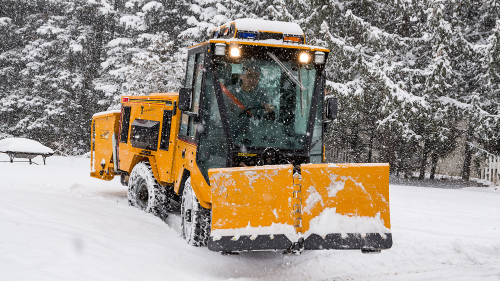 trackless vehicles 5-position folding v-plow attachment on sidewalk tractor in snow front view
