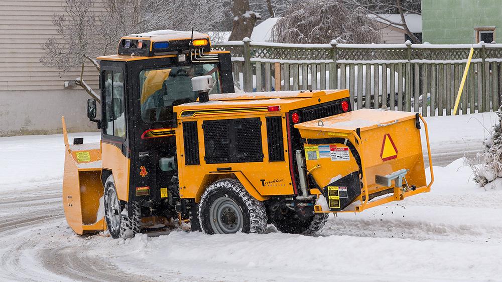 trackless vehicles rear-mount sidewalk spreader attachment on sidewalk tractor in snow