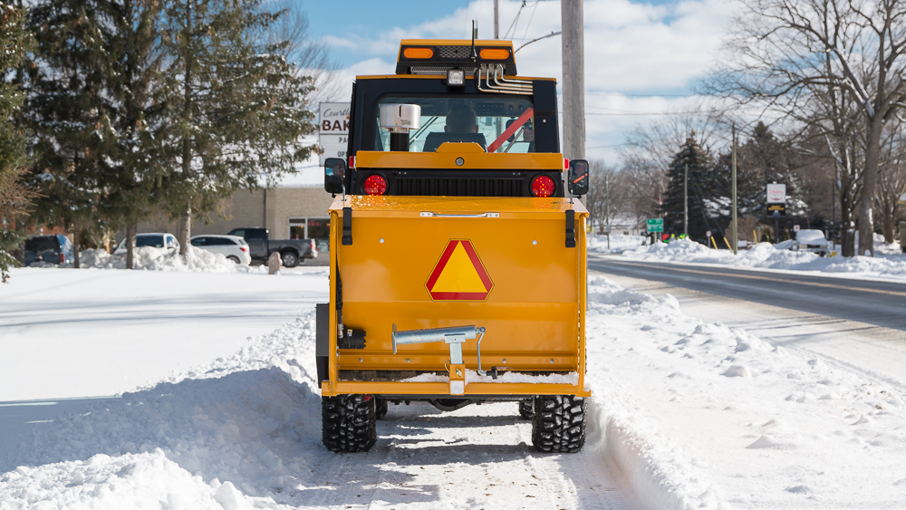 trackless vehicles rear-mount sidewalk spreader attachment on sidewalk tractor in snow rear view