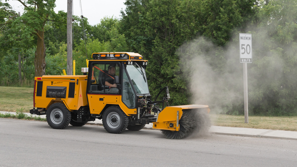 trackless vehicles power angle sweeper attachment on sidewalk municipal tractor moving dirt on road