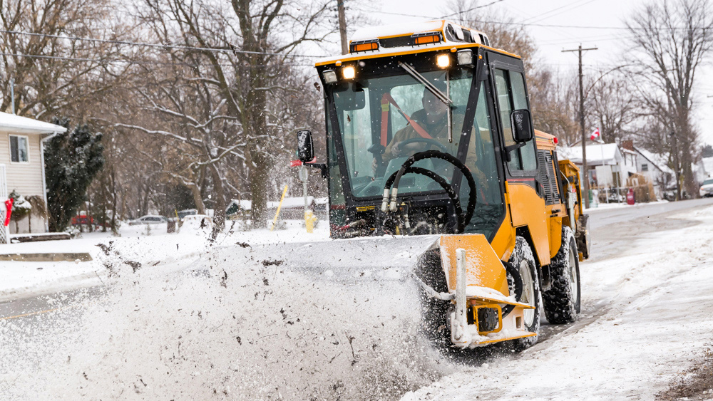 trackless vehicles power angle sweeper attachment on sidewalk municipal tractor moving snow on sidewalk front view