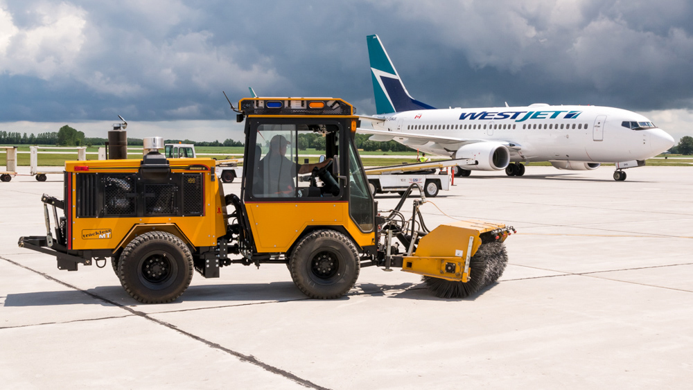 trackless vehicles power angle sweeper attachment on sidewalk municipal tractor at airport