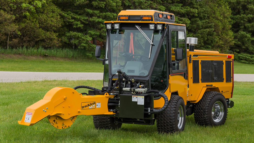 trackless vehicles stump grinder attachment on sidewalk municipal tractor front view