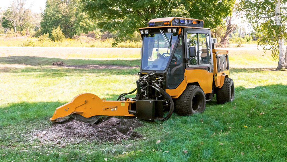 trackless vehicles stump grinder attachment on sidewalk municipal tractor grinding stump front view
