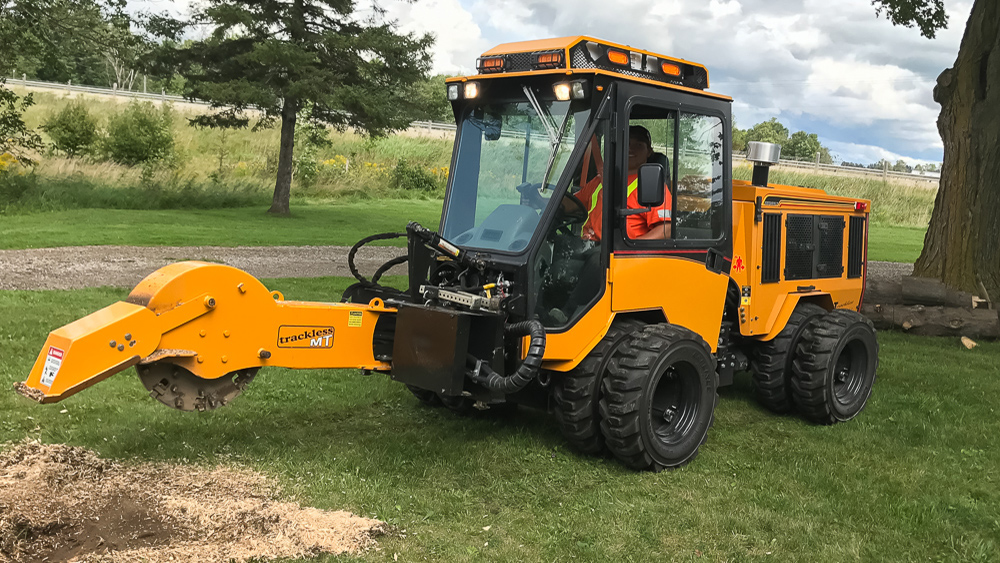 trackless vehicles stump grinder attachment on sidewalk municipal tractor grinding stump side view