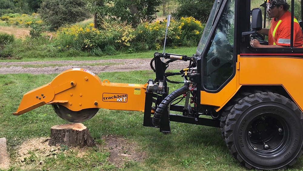 trackless vehicles stump grinder attachment on sidewalk municipal tractor grinding stump side view close-up