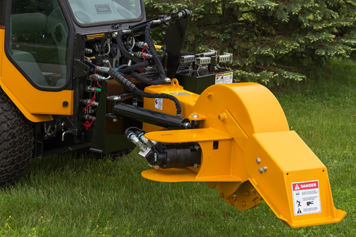 trackless vehicles stump grinder attachment on sidewalk municipal tractor close-up front side view
