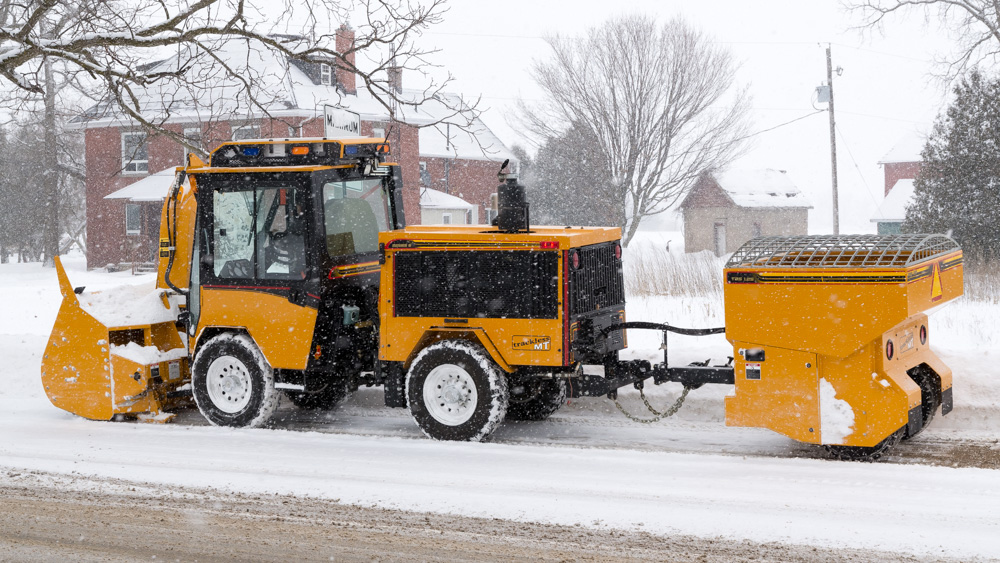 trackless vehicles tow behind spreader attachment on sidewalk tractor in snow side view