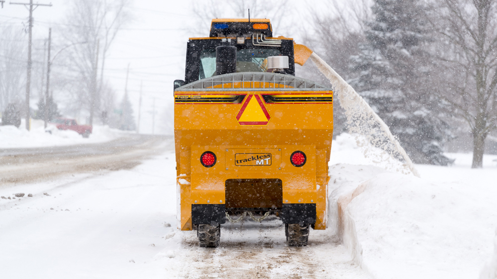trackless vehicles tow behind spreader attachment on sidewalk tractor in snow rear view