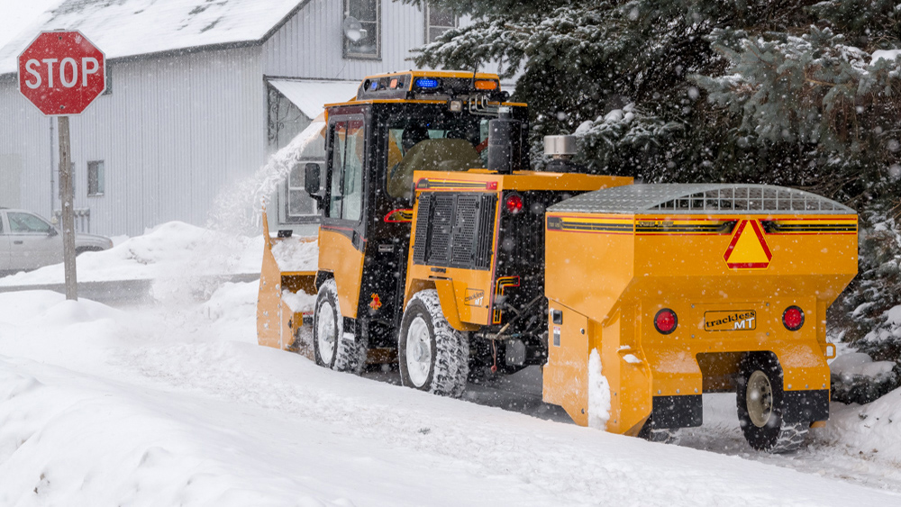 trackless vehicles tow behind spreader attachment on sidewalk tractor in snow