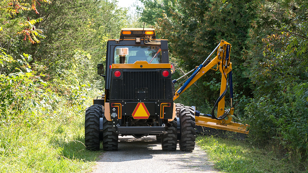 trackless vehicles boom flail mower attachment on sidewalk municipal tractor mowing grass rear view