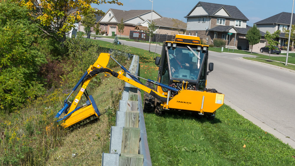 trackless vehicles boom flail mower attachment on sidewalk municipal tractor mowing grass in ditch front view