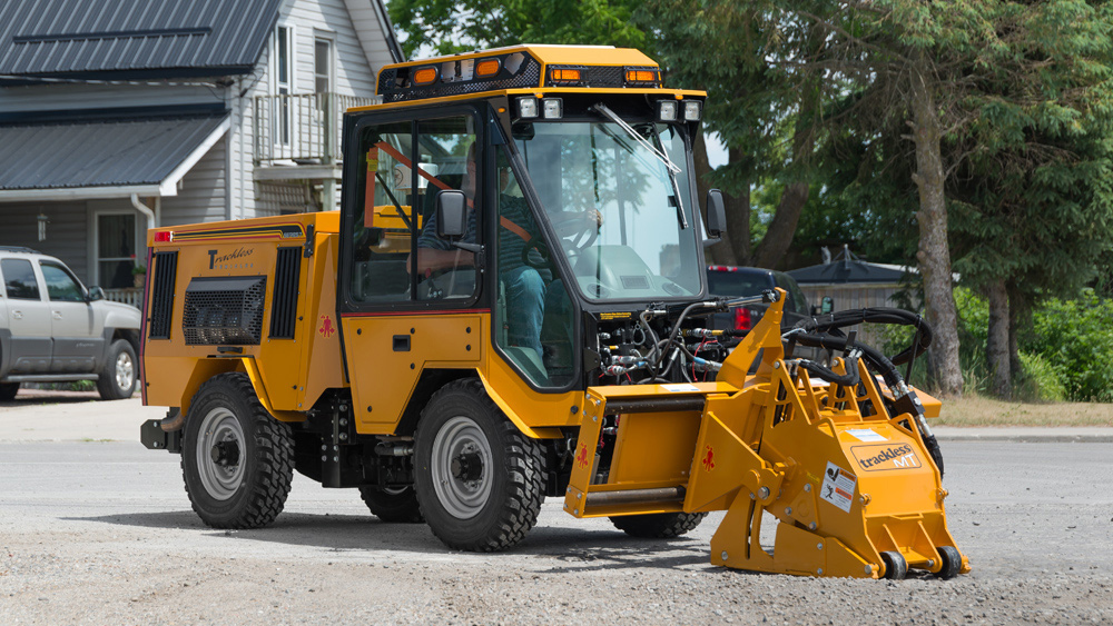 trackless vehicles cold planer attachment on sidewalk tractor side view