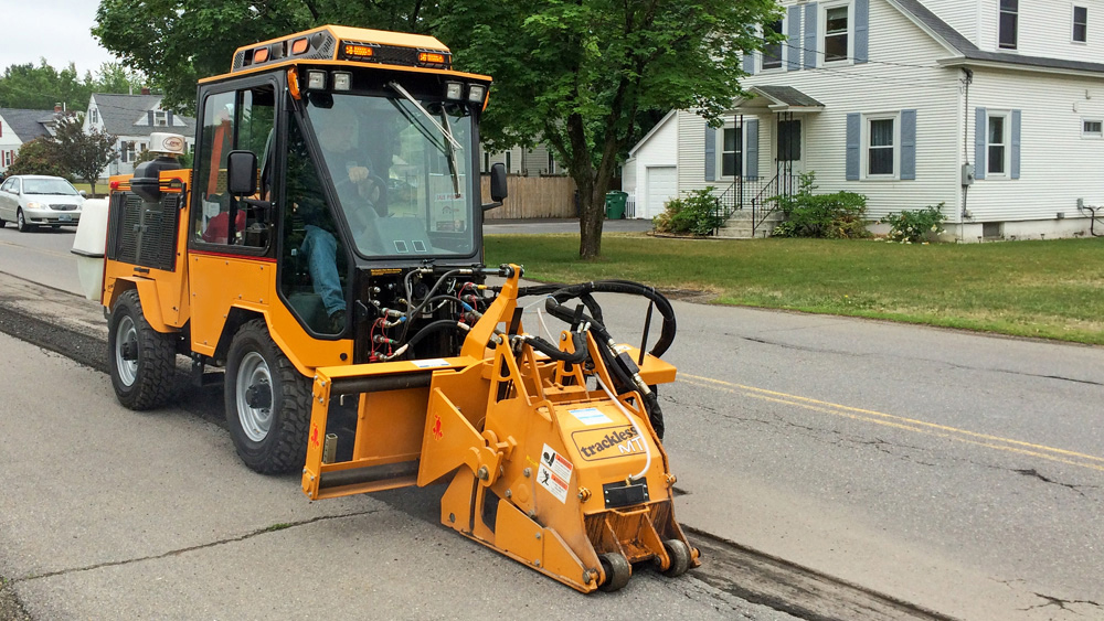 trackless vehicles cold planer attachment on sidewalk tractor working on sidewalk side view