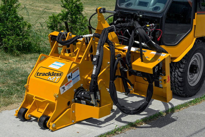 trackless vehicles cold planer attachment on sidewalk tractor working on sidewalk side view close-up